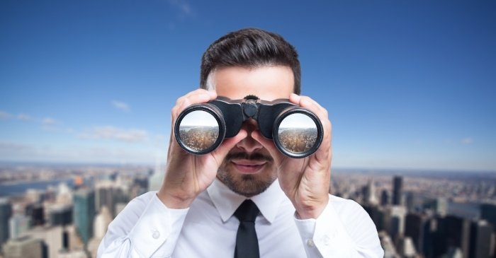 Man Looking Through Binoculars with a City Behind Him