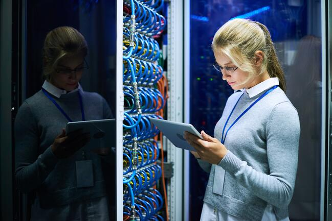 Woman in server room managing IT orchestration