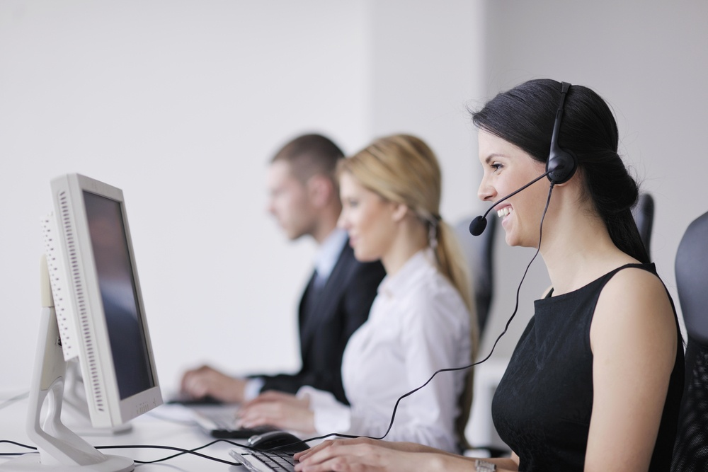 contact center agents helping customers over phone wearing headsets