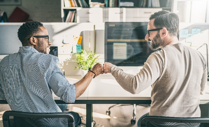 two male colleagues collaborating giving each other fist bump unified communications partner
